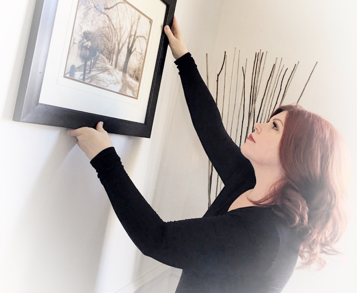 Award Winning Home Stager, Teresa Meyer, at work hanging a black and white print